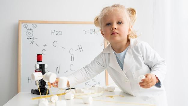 Schattige peuter die over wetenschap leert met whiteboard en microscoop