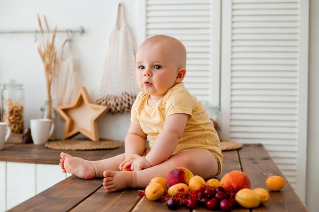 Schattige peuter eet fruit in houten keuken thuis
