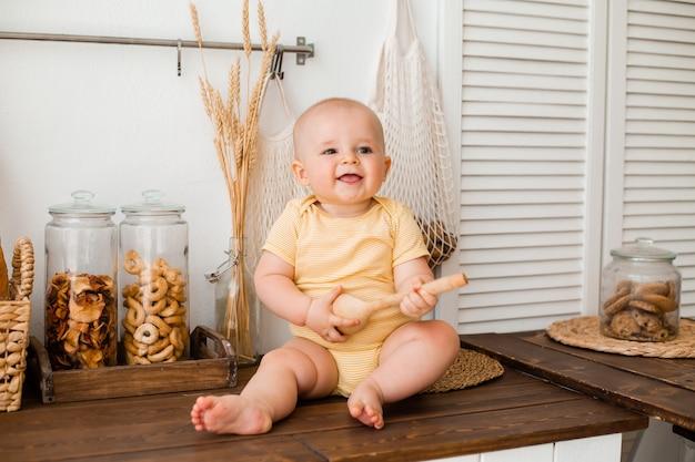Schattige peuter in de houten keuken van het huis