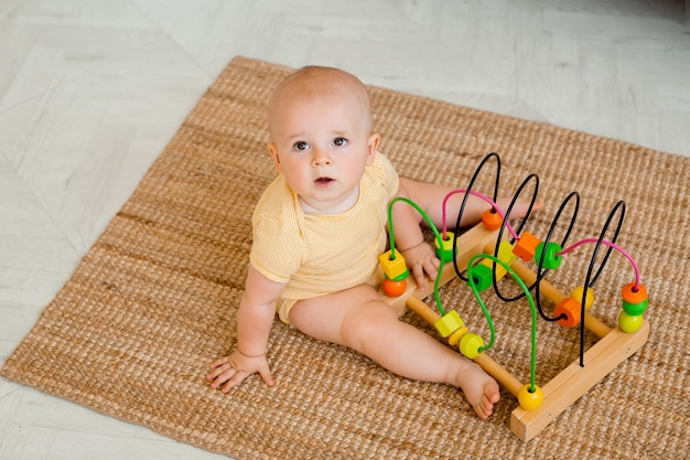 Schattige peuter in gele romper zit thuis op de vloer spelen in een zich ontwikkelend speelgoed. kind ontwikkelingsconcept
