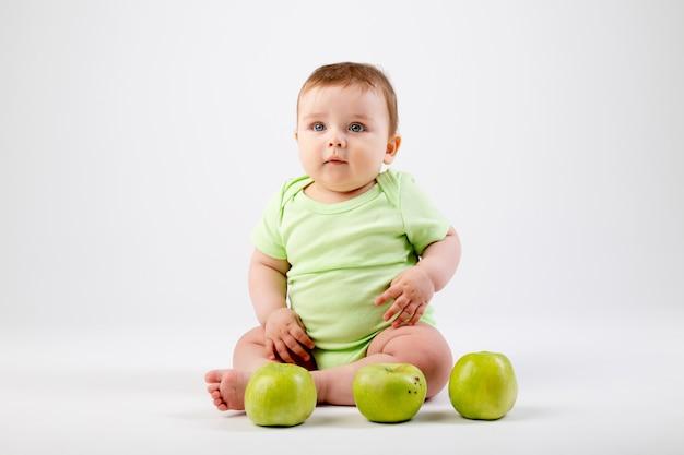 Schattige peuter in groene romper zit met groene appels