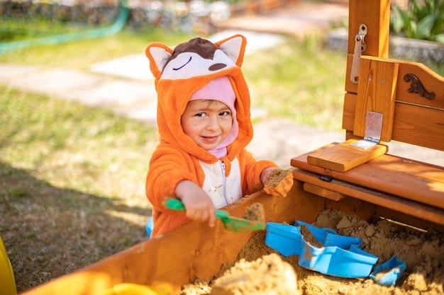 Schattige peuter in oranje jumpsuit speelt in het zand in de zandbak buiten op een zonnige dag