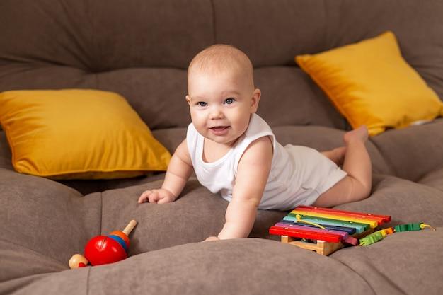Schattige peuter in witte bodysuit ligt thuis op een grijze bank met gele kussens die spelen met houten ontwikkelingsspeelgoed