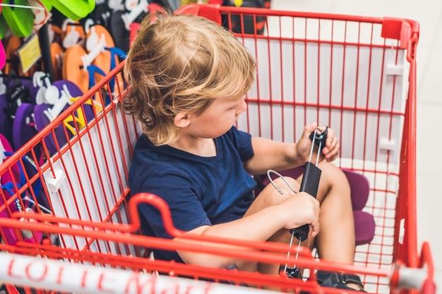 Schattige peuter jongen zit in de winkelwagen in een levensmiddelenwinkel of een supermarkt.