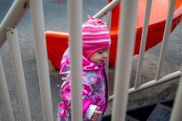 Schattige peuter klimt de trap op de speelplaats. peuter baby gekleed in een snowsuit. herfst of winter, koud seizoen