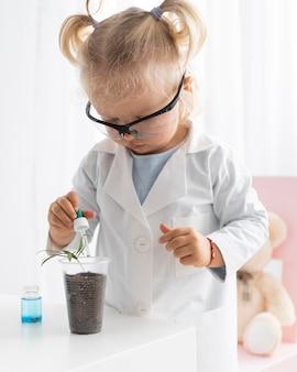 Schattige peuter leren over wetenschap met plant