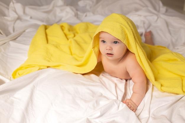Schattige peuter ligt in bed met gele handdoek na het baden