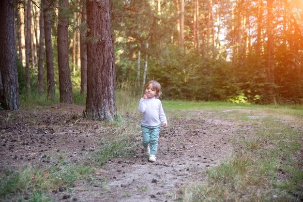 Schattige peuter loopt in het bos
