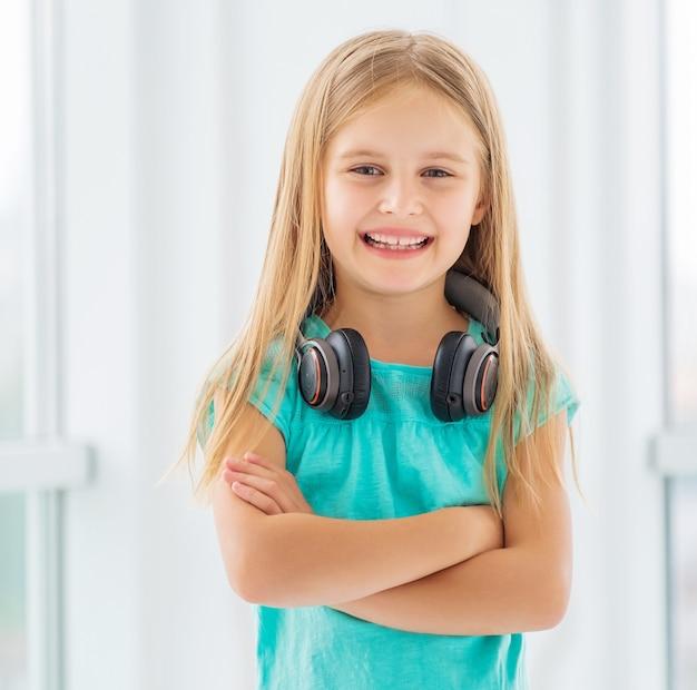 Schattige peuter meisje met koptelefoon lacht en poseren