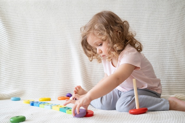 Schattige peuter meisje spelen met houten speelgoed zittend op de bank.