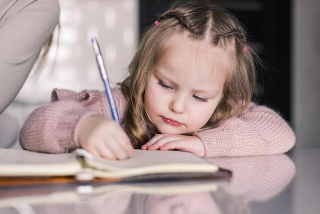 Schattige peuter meisje tekenen met pen aan tafel