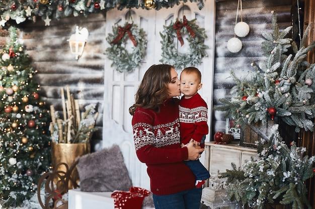 Schattige peuter op de handen van zijn mooie moeder bij kerstinterieur