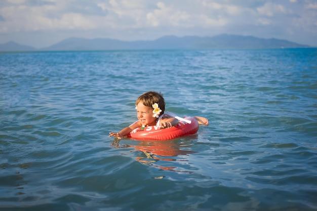 Schattige peuter peuter zwemt in de zee in een speciale opblaasbare reddingsring
