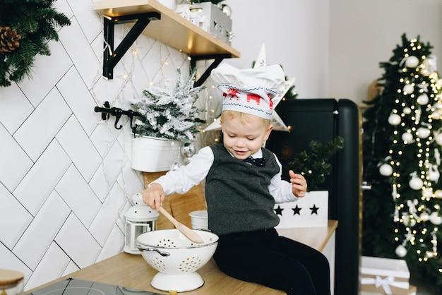 Schattige peuter zittend op een aanrecht in de keuken