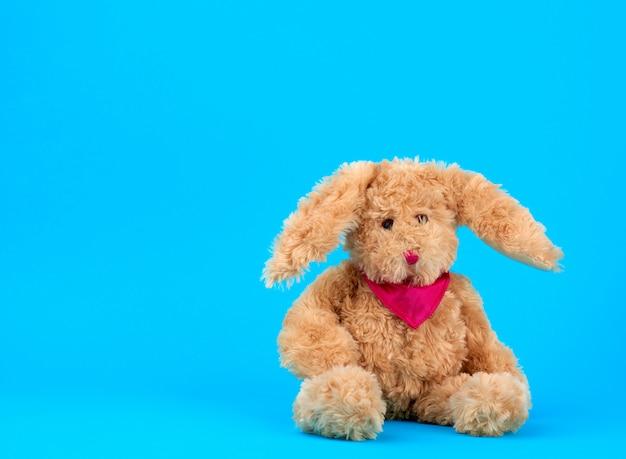 Schattige pluche beige konijn met een roze stropdas zit op blauw