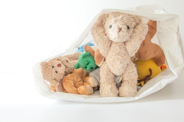 Schattige pop speels in wit plastic zak, teddybeer verstoppertje spelen met een beste vriend 's ochtends plezier hebben
