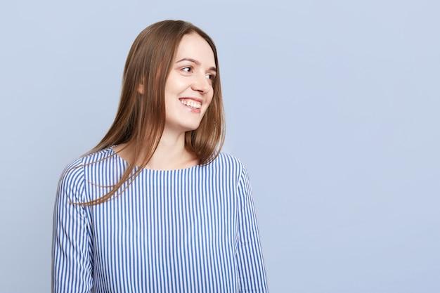 Schattige positieve vrouw in gestreepte elegante blouse ziet er met vrolijke uitdrukking opzij, ziet iets aangenaams, geïsoleerd op blauw met kopie ruimte voor uw advertentie of tekst