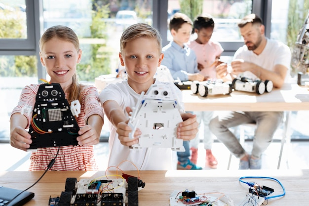 Schattige pre-tiener kinderen inspecteren werkplaats voor robotvoertuigen