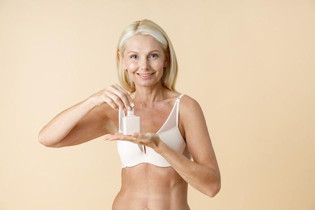 Schattige rijpe vrouw in ondergoed die een witte pot huidverzorgingscrème of -lotion vasthoudt en opent