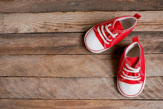 Schattige rode babymeisje sneakers op bruine houten achtergrond met kopie ruimte
