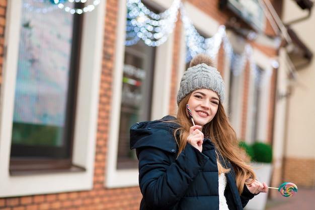 Schattige roodharige jonge vrouw die een grijze gebreide muts draagt en kleurrijke kerstsnoepjes vasthoudt in de buurt van de etalage
