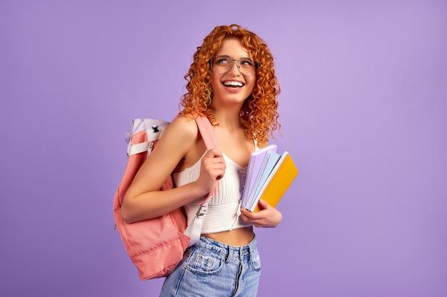 Schattige roodharige krullend studente tiener met een rugzak houdt notitieblokken en notebooks geïsoleerd op een paarse muur.