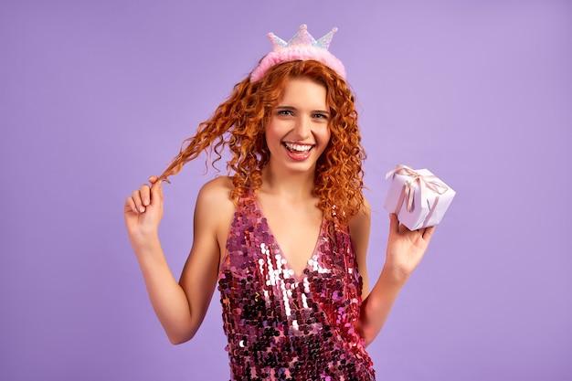 Schattige roodharige meisjesprinses met krullen in een glanzende jurk en een kroon op haar hoofd met een geschenk geïsoleerd op paars Premium Foto