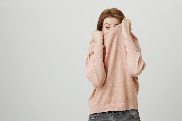 Schattige roodharige tiener meisje verbergt gezicht over trui, gluren