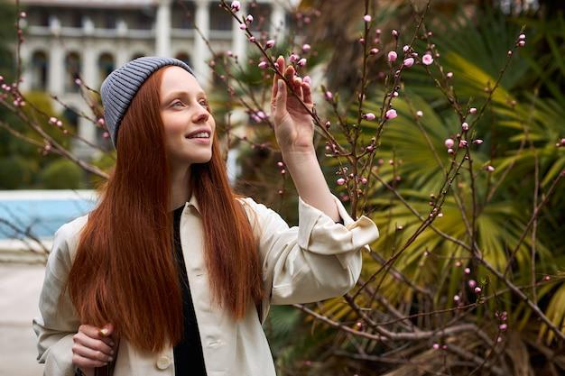 Schattige roodharige vrouw in hoed poseren in bloeiende boom in het voorjaar mooie gelukkige jonge vrouw geniet...