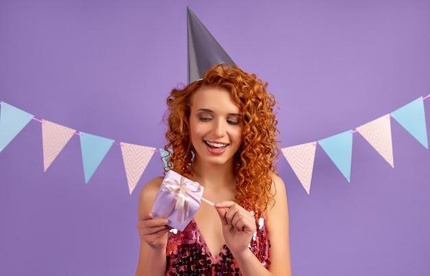 Schattige roodharige vrouw met krullen in een glanzende jurk en een feestmuts opent haar geschenk geïsoleerd op paars
