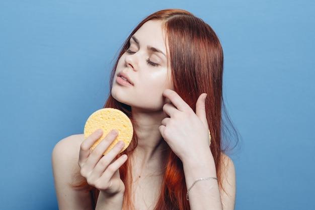 Schattige roodharige vrouw naakte schouders veegt gezicht met spons huidverzorging.