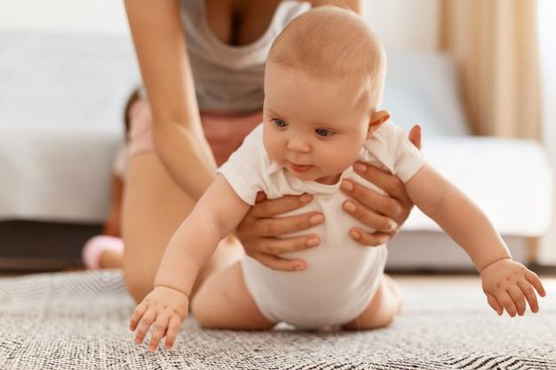 Schattige schattige baby in witte romper kruipend op de vloer op tapijt terwijl moeder helpt en ondersteunt, poseren in lichte kamer thuis, gelukkige jeugd.