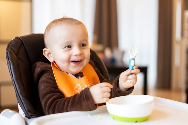 Schattige schattige baby plastic vork in zijn hand nemen en spelen met voedsel zittend in de hoge stoel.