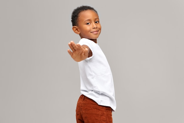Schattige schattige donkere jongen hand reiken stop gebaar maken of afscheid. knappe afro-amerikaanse mannelijke kind gebaren, teken geven, bericht verzenden. non-verbale communicatie