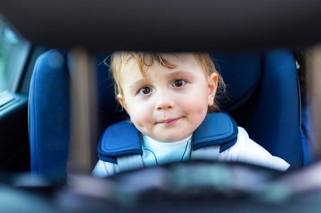 Schattige schattige glimlachende kleine jongen zit in de auto in een veiligheidsstoel