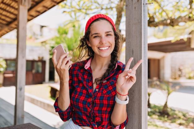 Schattige schattige jonge vrouw met gelukkige charmante glimlach met smartphone rust buiten in zonlicht en vredesteken vertoont. hipster levensstijl, zomerdag