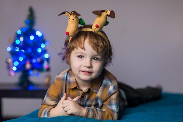 Schattige schattige jongen met hoorns van een hert op zijn hoofd viert het nieuwe jaar en kerstmis