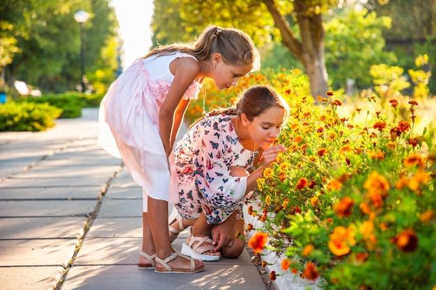 Schattige schattige meisjes in roze delicate jurken ruiken prachtige vurige goudsbloemen in een helder zomerpark op een zonnige dag op een langverwachte vakantie
