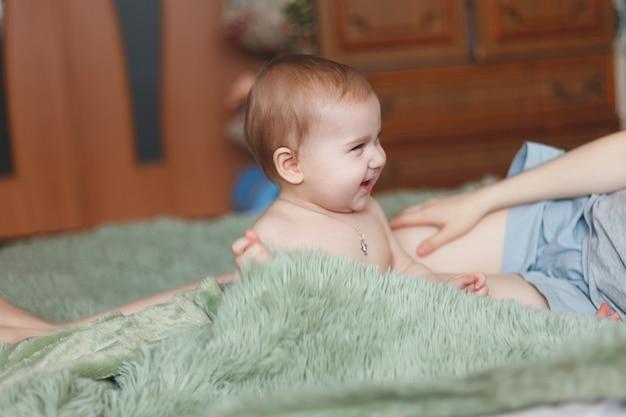 Schattige schattige pasgeboren baby van 3 motten met luiers. hapy uiterst klein meisje of jongen die de camera bekijken. droog en gezond lichaam en huid voor kinderenconcept. baby kwekerij