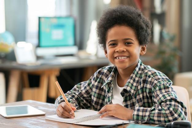 Schattige schooljongen van afrikaanse etniciteit die aantekeningen maakt in het schrijfboek en naar je kijkt met een glimlach terwijl hij huiswerk maakt aan tafel in de woonkamer