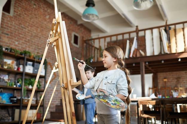 Schattige schoolmeisje schilderen