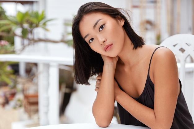 Schattige serieuze aziatische vrouw heeft een serieuze uitdrukking, poseert alleen in een café, verveelt zich in onbekend land, is nonchalant gekleed, heeft goede recreatie.