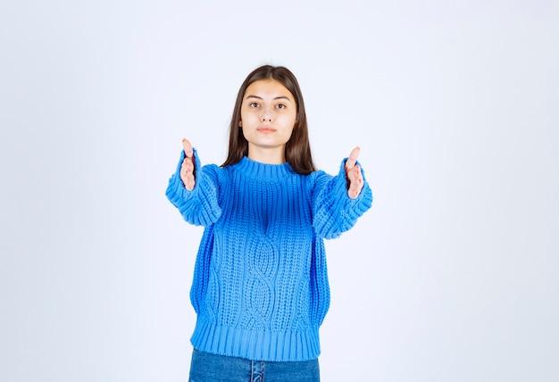Schattige serieuze vrouw strekt handen uit en kijkt direct naar de camera.