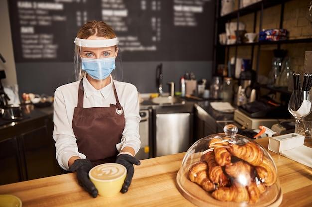 Schattige serveerster met een medisch masker die voorzichtig een kopje cappuccino op een toog aanraakt. rubberen handschoenen aan haar handen