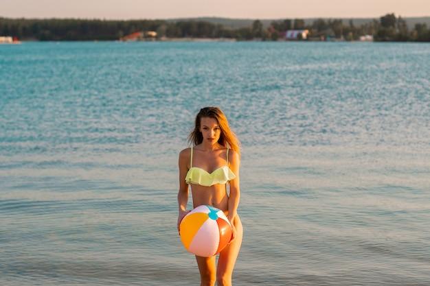 Schattige slanke dame in zwembroek met strandbal in de zee bij warme zonsondergang