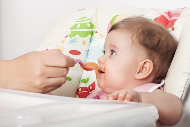 Schattige smoezelige vrouwelijke baby die haar favoriete eten eet