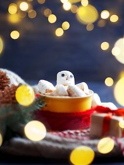 Schattige sneeuwpop marshmallow in een kop warme koffie of chocolademelk met een rode sjaal