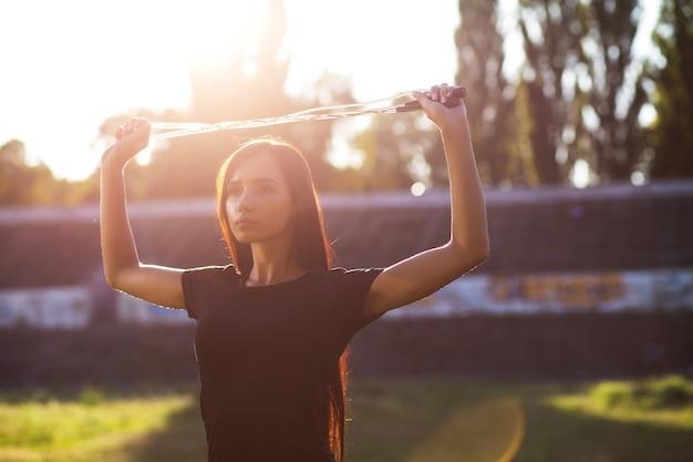 Schattige sportieve vrouw die zich uitstrekt voor de training in het stadion. buiten geschoten met zonnestralen. ruimte voor tekst