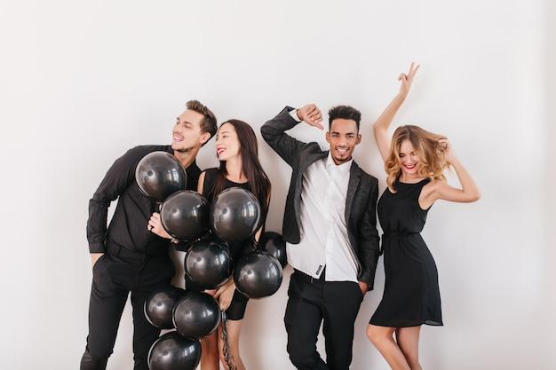 Schattige stellen in zwarte kleding wegkijken met glimlach terwijl poseren op een witte muur