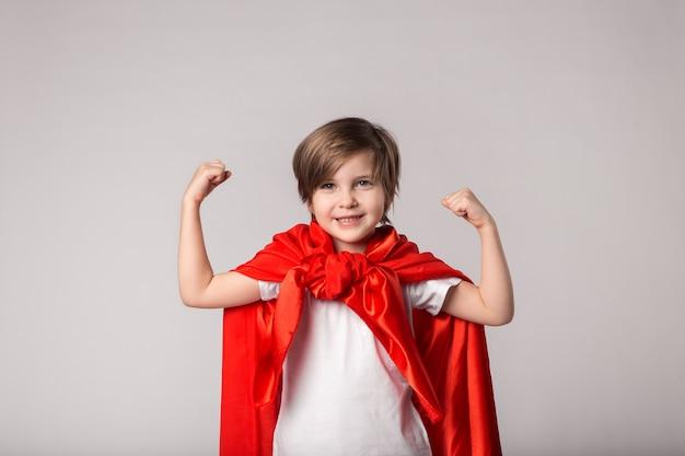 Schattige superwoman jongen in rode cape toont haar spieren